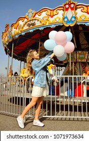 Beautiful young woman with colorful balloons in the amusement park