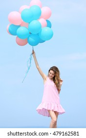 Beautiful young woman with colorful balloons against blue sky