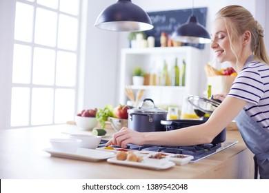Schöne junge Frau, die zu Hause in der Küche kocht