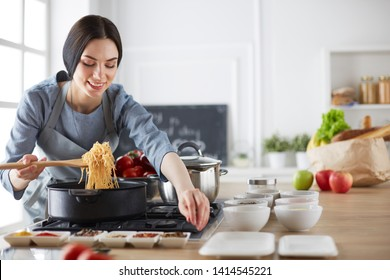 Beautiful young woman cooking in kitchen at home.