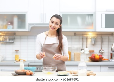 Beautiful young woman cooking in kitchen