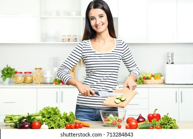 Beautiful young woman cooking salad in the kitchen