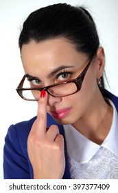 Beautiful, young woman corrects glasses middle finger.