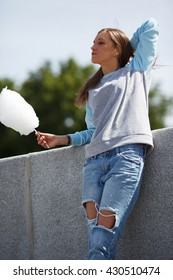 Beautiful young woman with cotton candy, outdoor. Natural blonde hair and natural make-up. Summer shot,