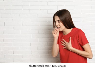 Beautiful young woman coughing near brick wall. Space for text