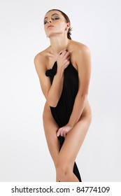 Beautiful young woman is covered with black cloth.