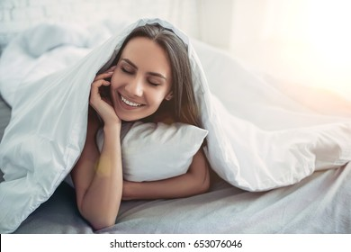 Beautiful young woman covered by blanket is lying on bed with eyes closed and smiling