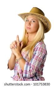 Beautiful young woman in cowboy dress showing gun by hands