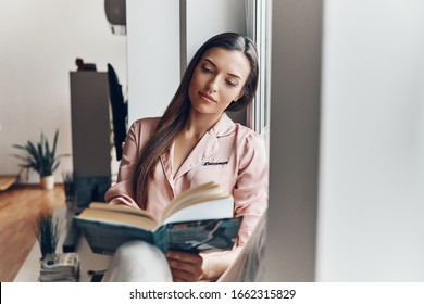Beautiful young woman in cozy pajamas reading a book while resting on the window sill at home
