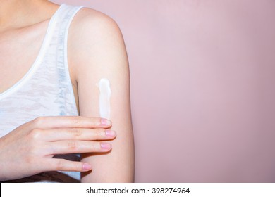Beautiful young woman with cream on her shoulder. Focus is on a hand with soft pink background