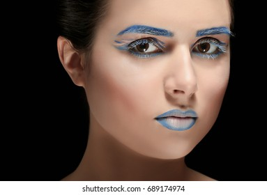 Beautiful young woman with creative make up on black background