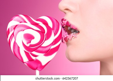 Beautiful young woman with creative makeup and lollipop on color background, closeup