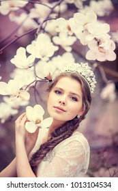 Beautiful young woman with crown in blossom magnolia garden. Spring.