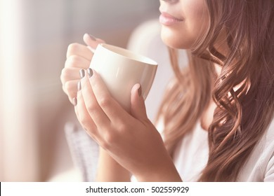 Beautiful young woman with cup of coffee at home