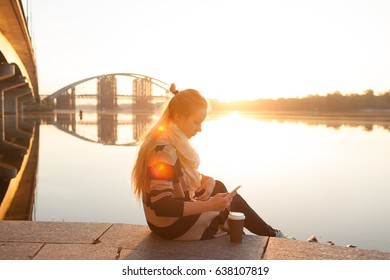 Beautiful young woman with cup of coffee and mobile phone sitting on a stairs near the river. Selective focus