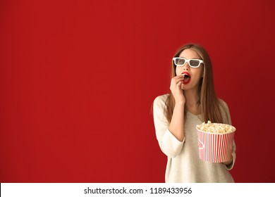 Beautiful young woman with cup of popcorn and 3D cinema glasses on color background