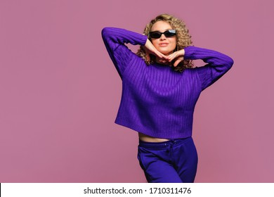 beautiful young woman   with curl hair in knitted violet sweater posing   on pink   background  with black glasses