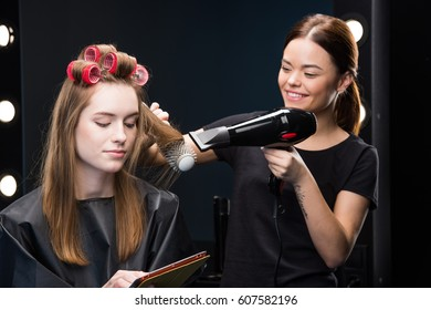 Beautiful young woman in curlers using digital tablet at hairdresser