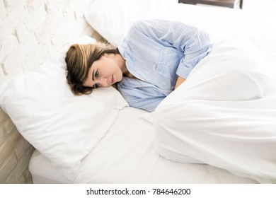 Beautiful young woman curling up on her bed while feeling unwell in the morning