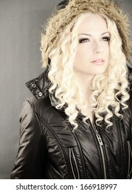 Beautiful young woman with curly blond hair wearing winter jacket