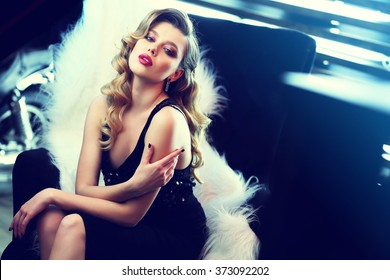 beautiful young woman with curly blond hair and bright makeup. Fashion studio shot. Retro fashion
