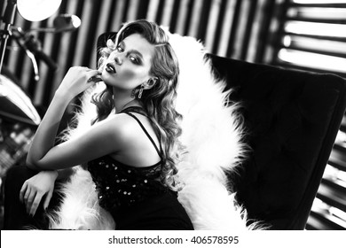 beautiful young woman with curly blond hair and bright makeup. Fashion studio shot. Retro fashion. Black and white image