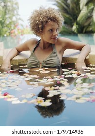 Beautiful young woman with a curly brown afro hairstyle relaxing in a pond with water lilies leaning back against the stone surround looking off frame to the right