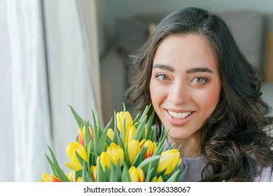 Beautiful young woman with curly hair holds a bouquet of tulips. Women's Day.