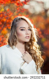beautiful young woman with curly hair against a background of red and yellow autumn leaves