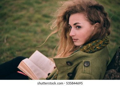 beautiful young woman with curly hair reads the book