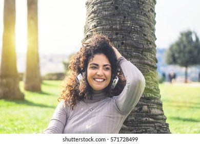 Beautiful young woman with curly hair listening to music with headphones leaning back on a palm tree in a park on a sunny day - Happy girl having nice moments relaxing outdoor
