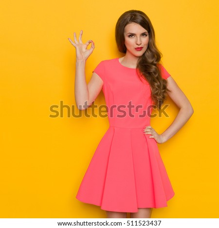 9cba243bbc79 Beautiful young woman with curly long brown hair in pink mini dress posing  with hand on