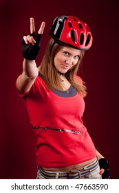 beautiful young woman cyclist in a red shirt and a helmet  with victory fingers