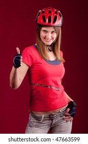 beautiful young woman cyclist in a red shirt and a helmet shows thumb