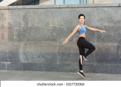 Beautiful young woman dancing against gray wall, copy space. Freedom spirit concept, copy space