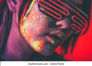 Beautiful young woman dancing and making party with fluorescent painting on her face. Neon facial portraits