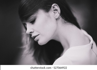 Beautiful young woman with dark hair and a beautiful neck bowed her head. Stylized film photography. Black and white photo.