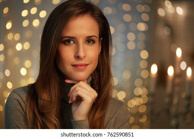 Beautiful young woman in a dark room with christmas lights.
