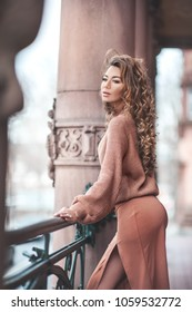 Beautiful young woman with dark sking and curly hair is posing in the city
