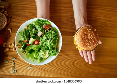 Beautiful young woman decides eating hamburger or fresh salad in kitchen. Cheap junk food vs healthy diet