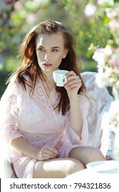 Beautiful young woman in delicate lace lingerie drink coffee in the spring apple garden in the morning