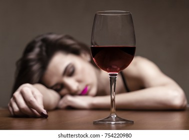 Beautiful young woman in depression with a glass of wine. Focus on the glass