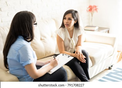 Beautiful young woman discussing her problems with female psychologist