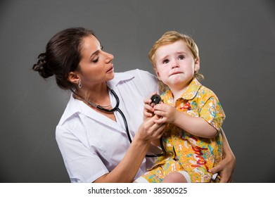 beautiful young woman doctor in a white coat holds a small child