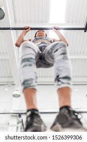 Beautiful and young woman does exercises in the box bar, calisthenics