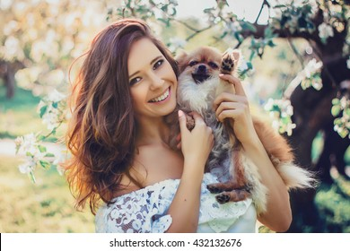Beautiful young woman with dog, young woman in spring blossom garden