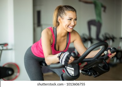 Beautiful young woman doing cardio on a stationary bike while smiling