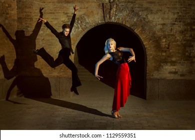 Beautiful young woman doing dance step, a young man makes a jump in dance.