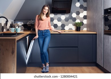Beautiful young woman doing dishes in a modern kitchen with dishwasher