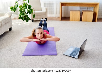 Beautiful young woman doing exercise for back on floor at home, online training on laptop computer, copy space. Full length portrait. Yoga, pilates, working out exercising